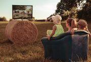 Familie schaut TV auf einem Feld